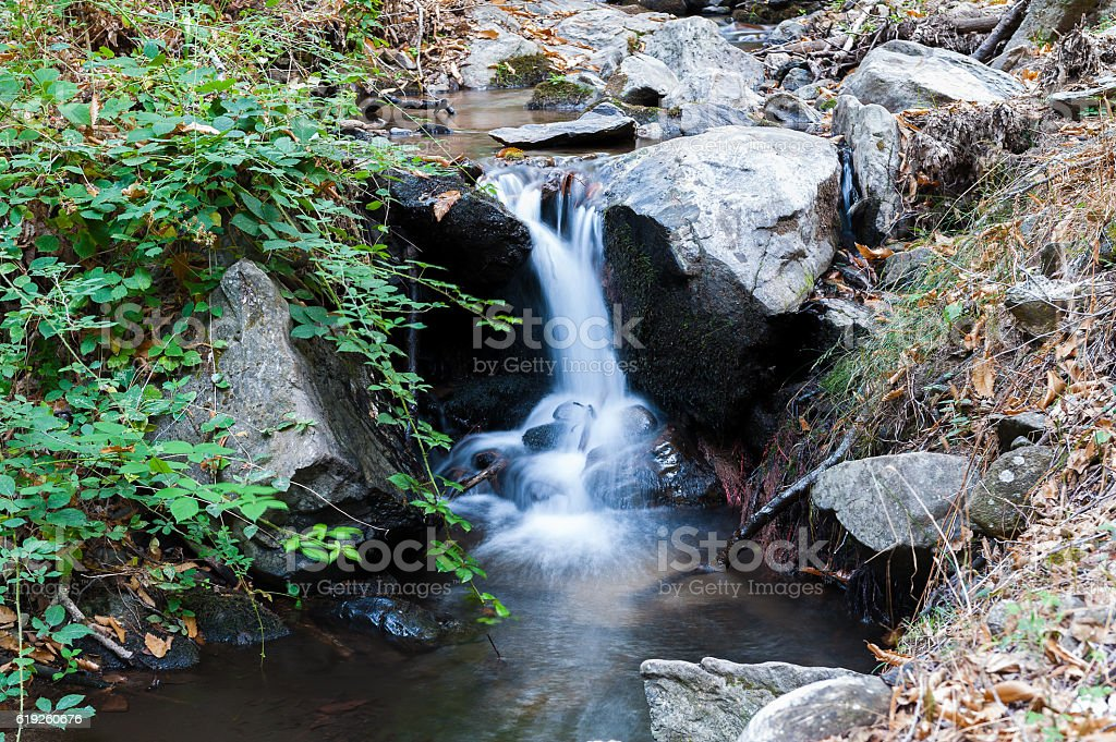 small river with waterfall on a green background trees stock photo