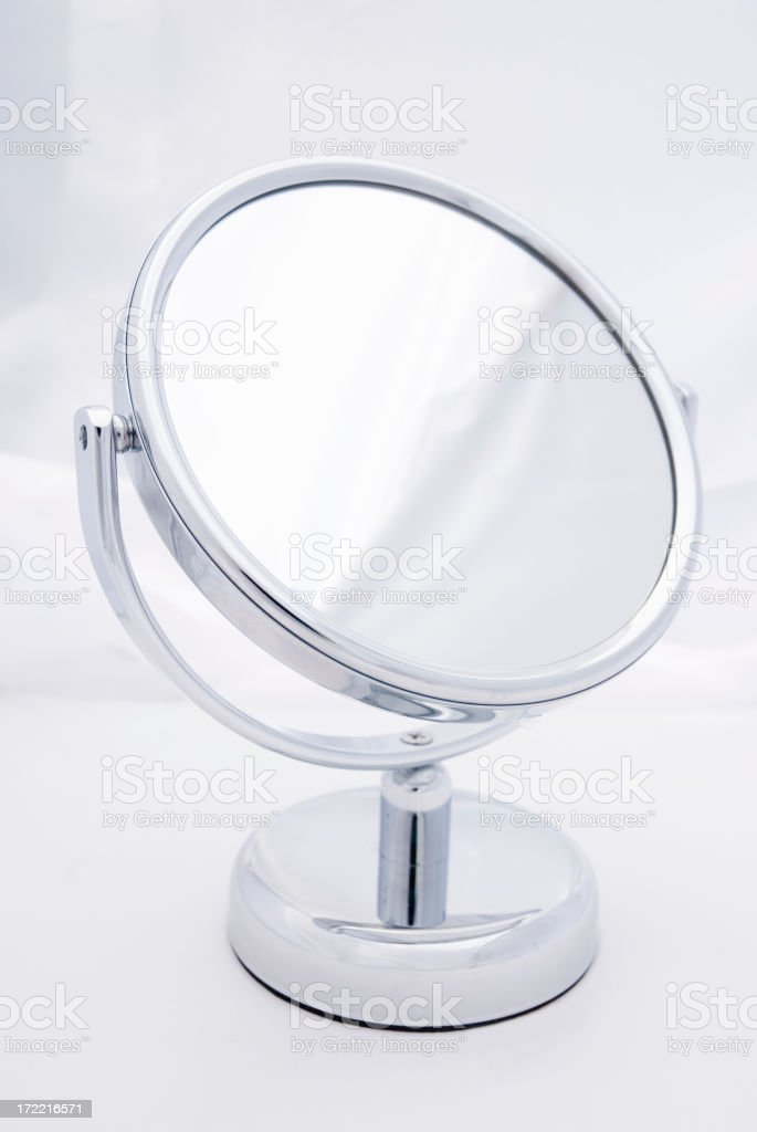 Small round looking glass (mirror), soft background, without any reflections stock photo