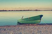 Small row boat on coastline during sunrise