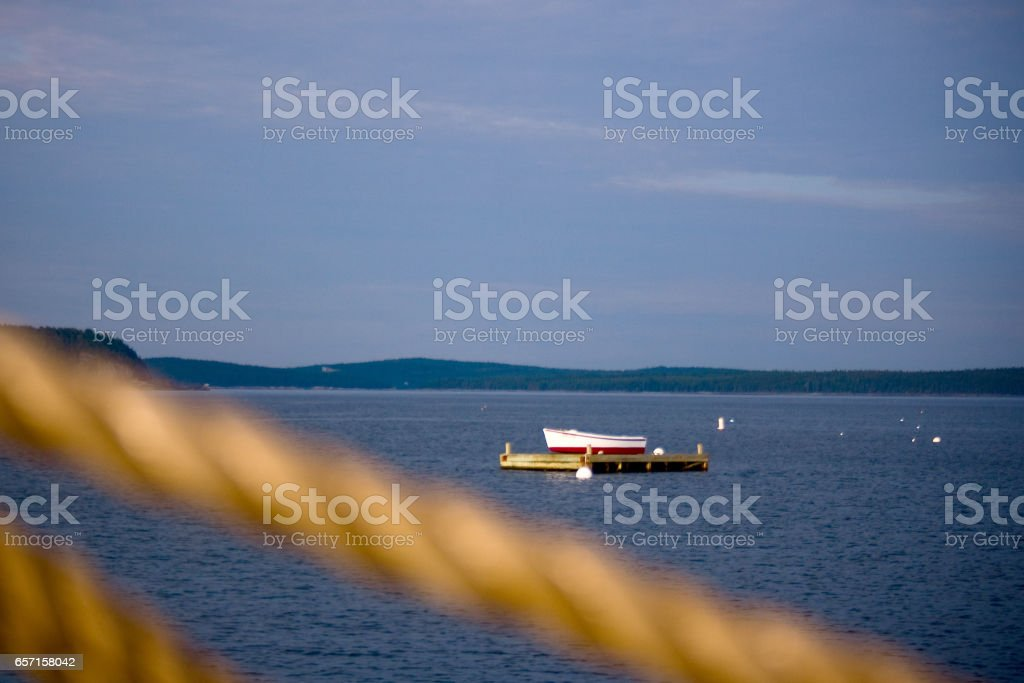Small Rowboat on Dock in Ocean with Rope in Foreground stock photo