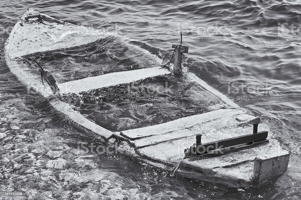 Small rowing boat submerged by sea water royalty-free stock photo