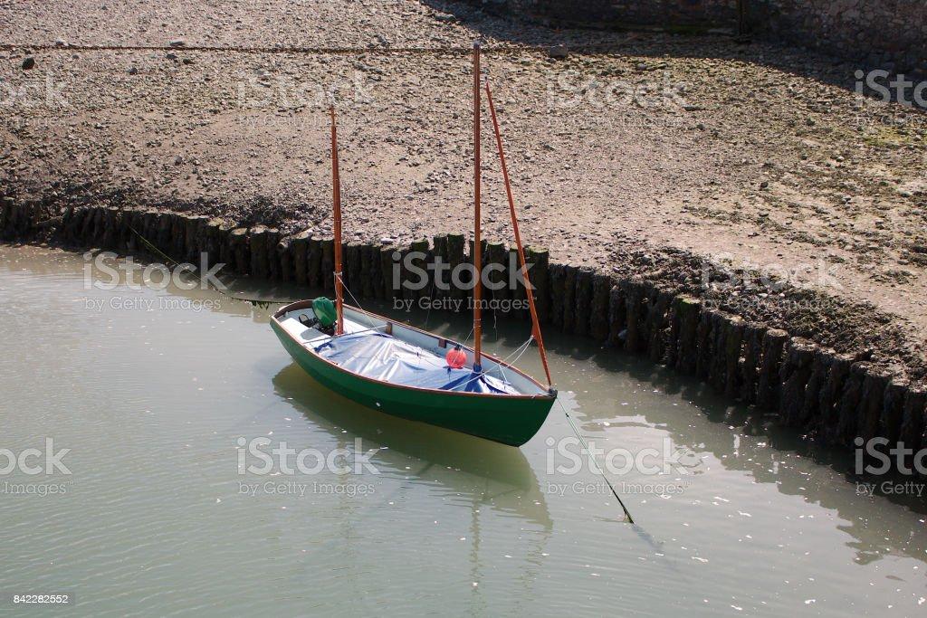 A small sail boat moored at anchor. stock photo