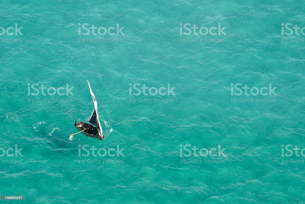 Small sailboat on a teal sea in Mozambique, Africa royalty-free stock photo