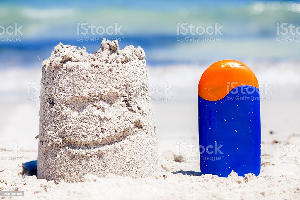 small sand castle and bronzing on the seashore during summer stock photo