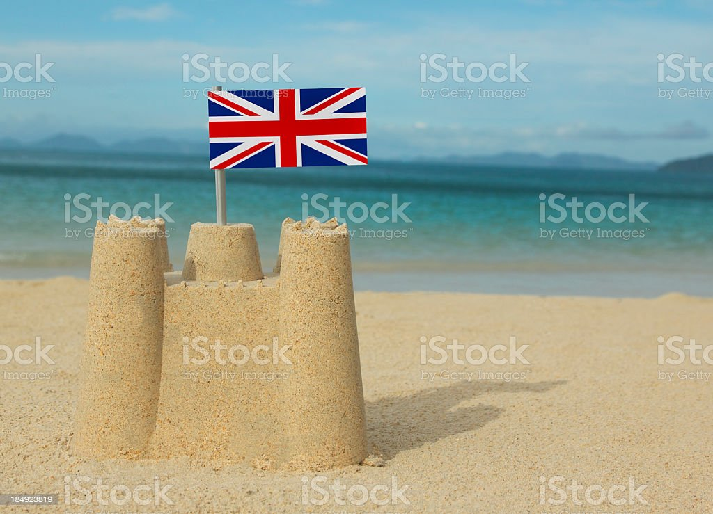 Small sandcastle with British flag in front of the ocean royalty-free stock photo