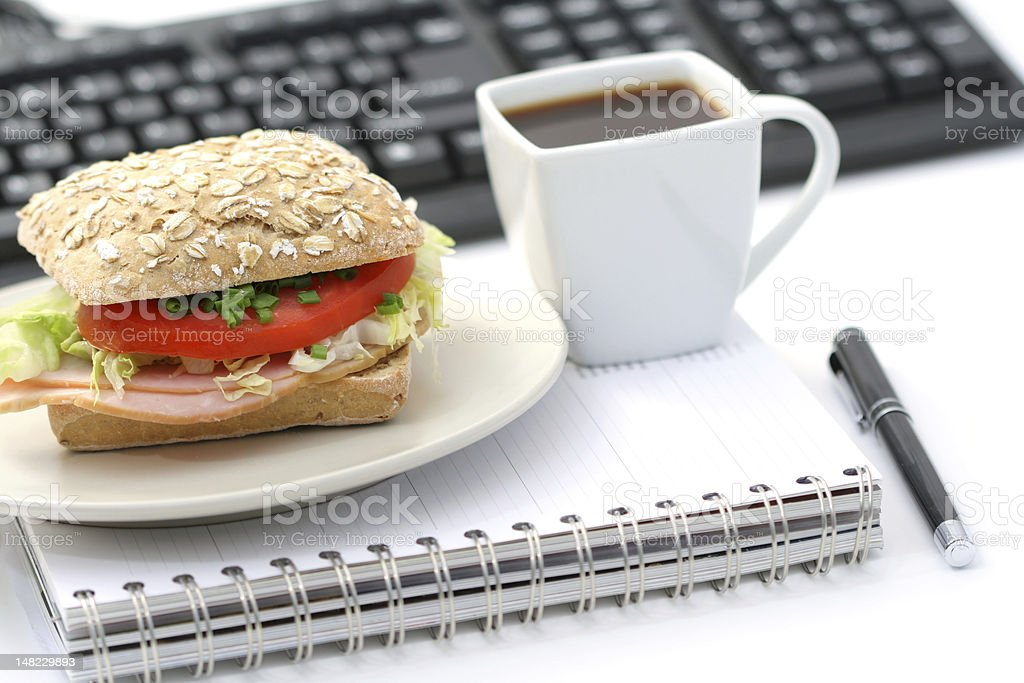 Small sandwich and cup of coffee sitting on a notepad royalty-free stock photo