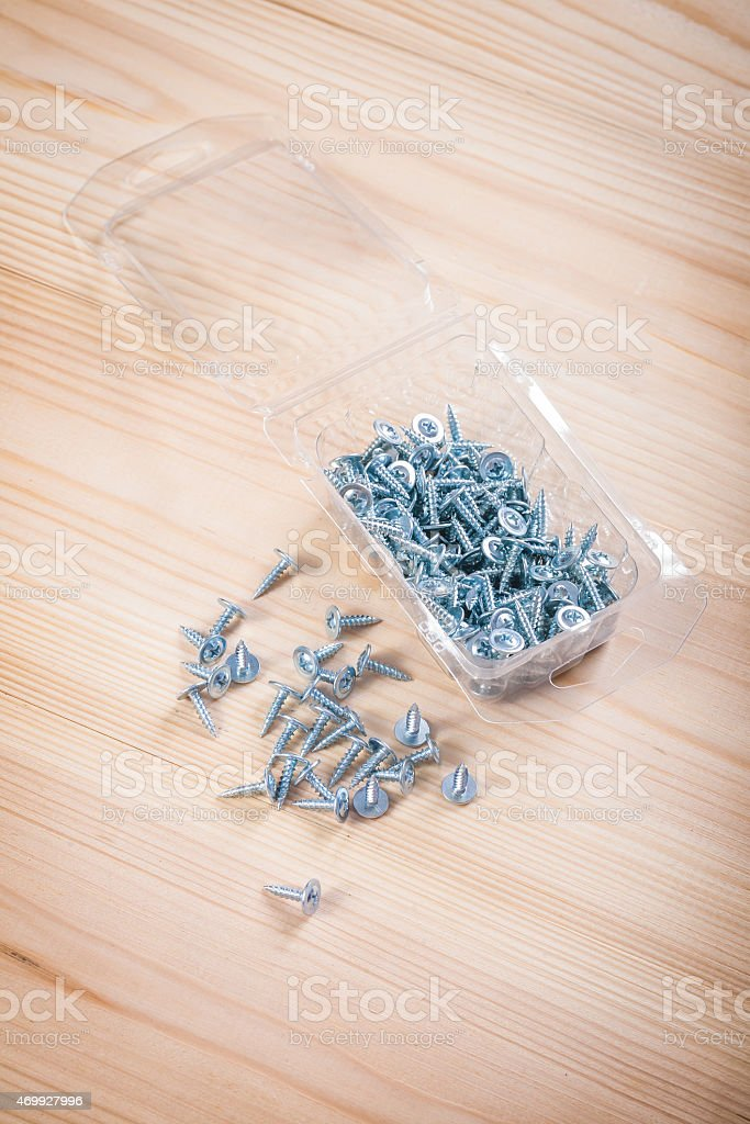 small screws in plastical box on wooden board stock photo