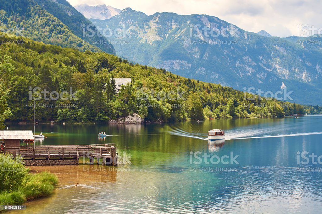 Small ship arrives to the wooden quay at lake Bohinj stock photo