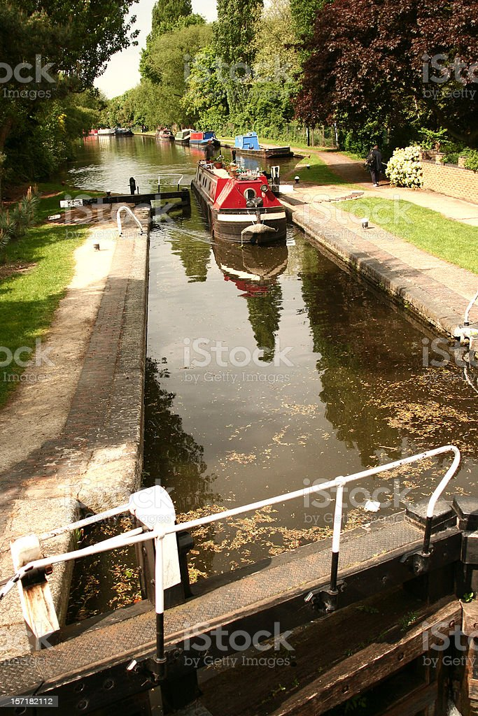 A small ship traversing a river lock royalty-free stock photo