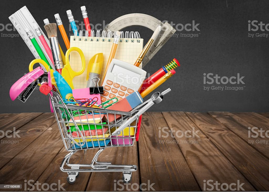 A small shopping cart filled with back to school supplies  stock photo