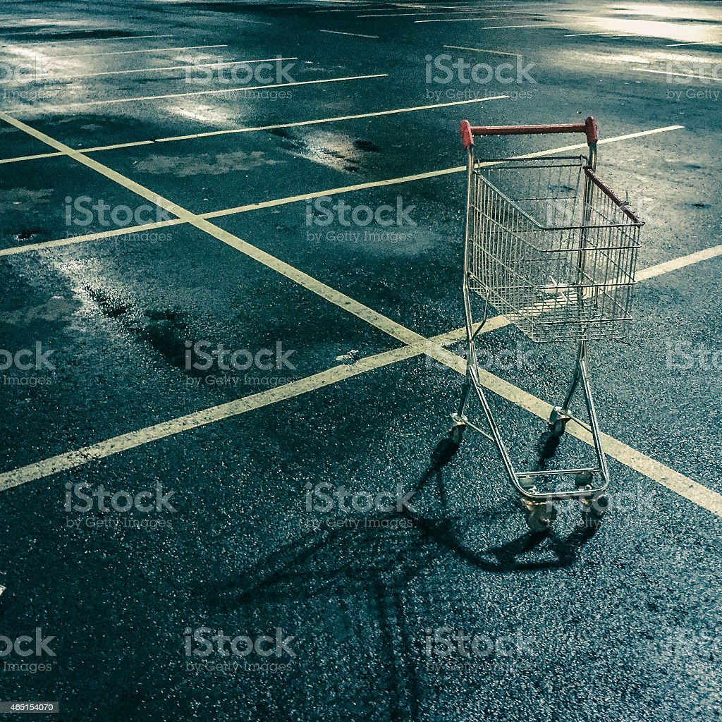 Small shopping cart in the parking lot. stock photo