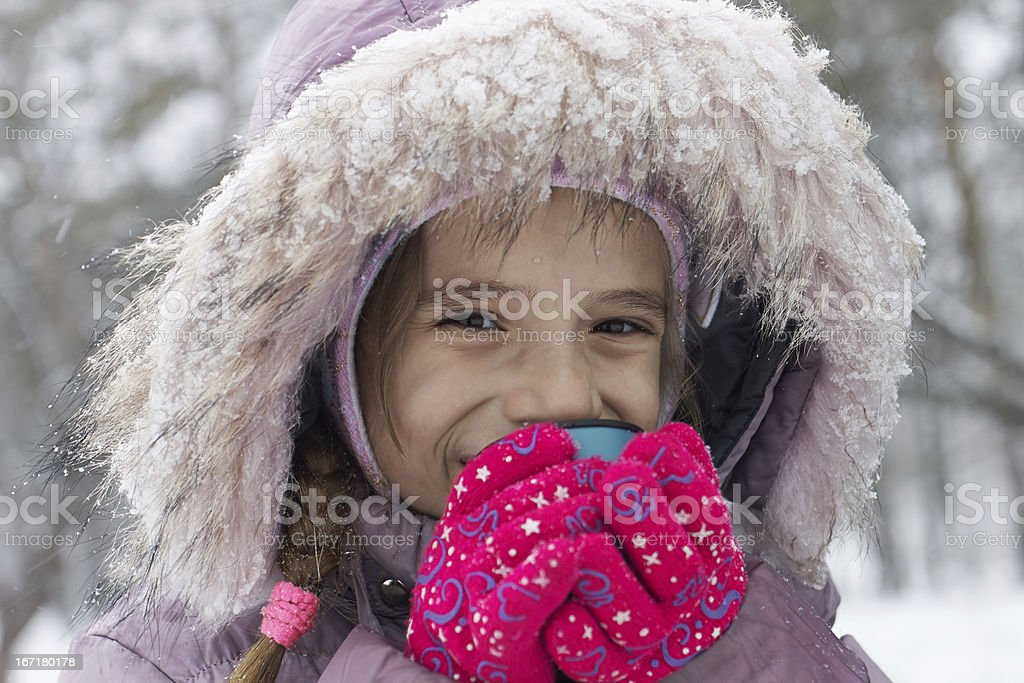 Small smiling girl drink hot tea in winter park royalty-free stock photo