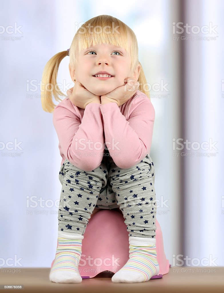 Small  smily girl sits  on a potty stock photo