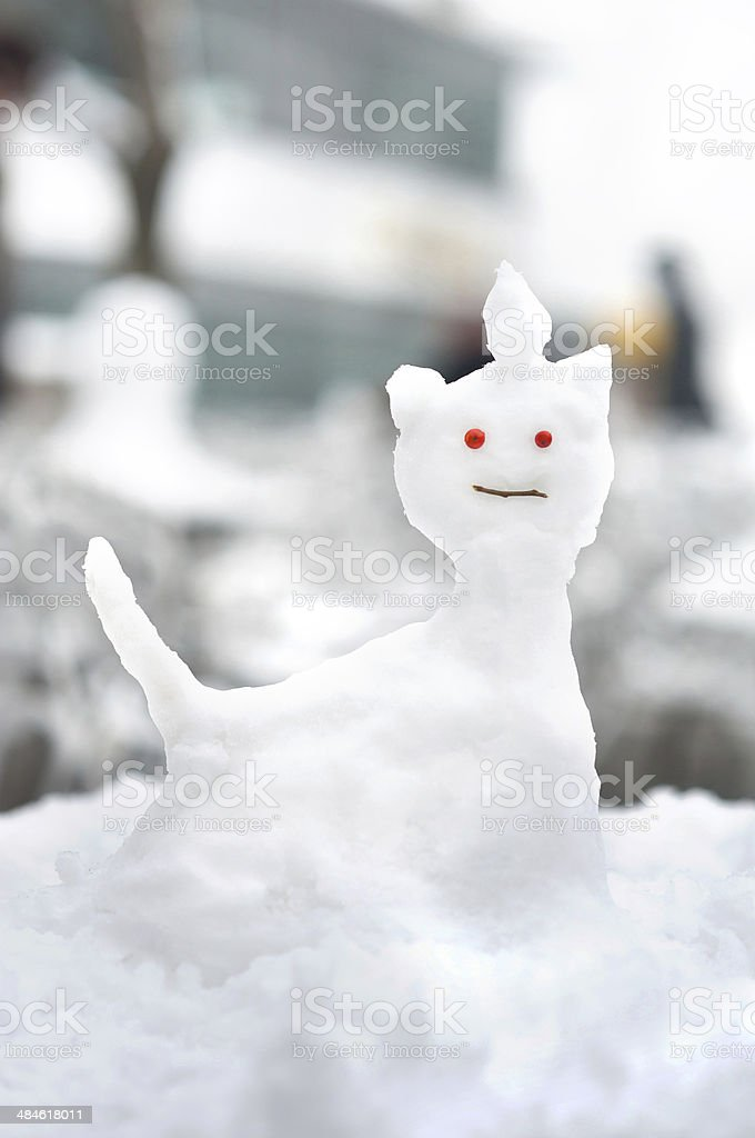Small snow sculpture in the shape of a cat stock photo