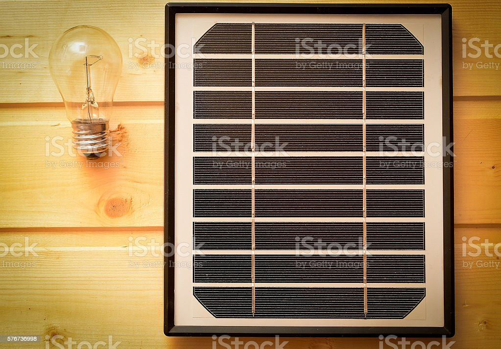small solar panel and a light bulb stock photo