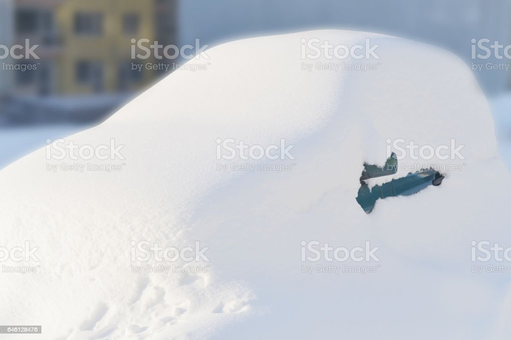 Small spark green car buried under snow. stock photo