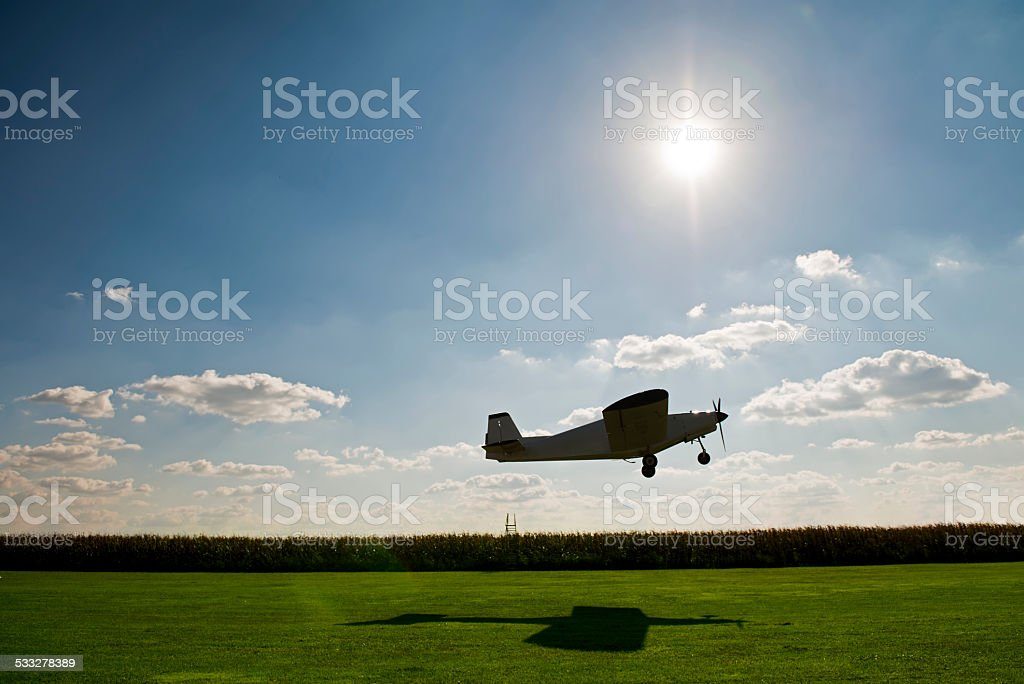 Small sport's airplane flying over  grass stock photo