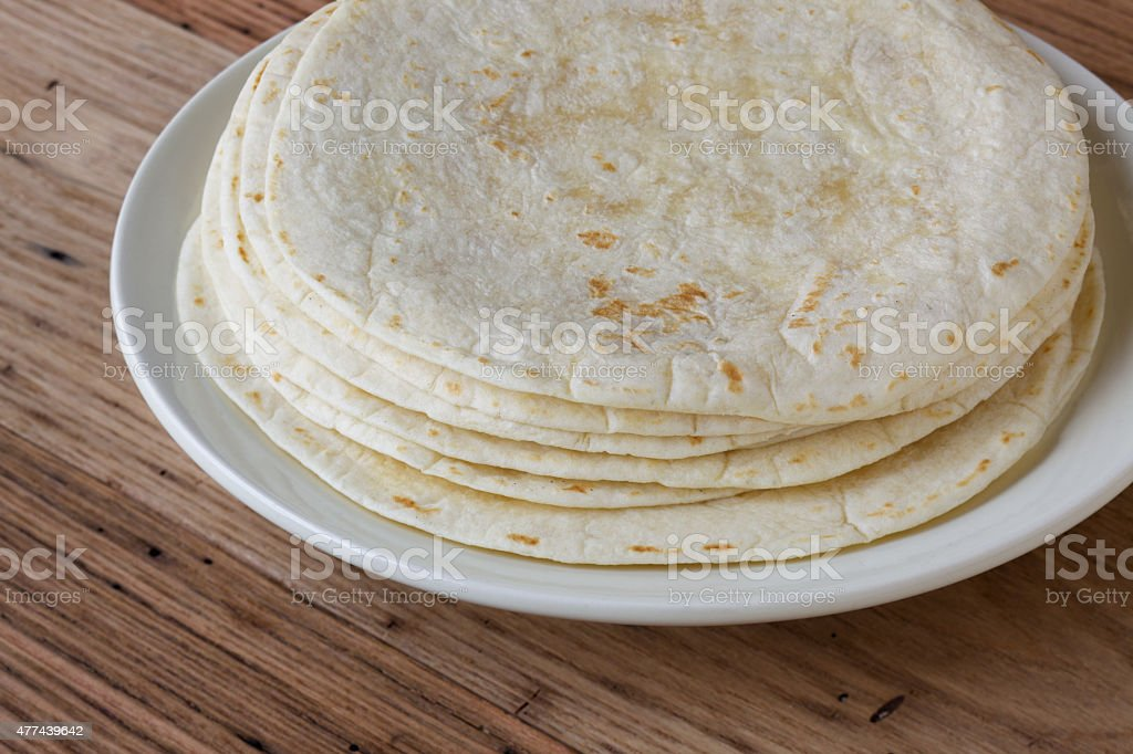 Small stack of flour tortillas on wood stock photo