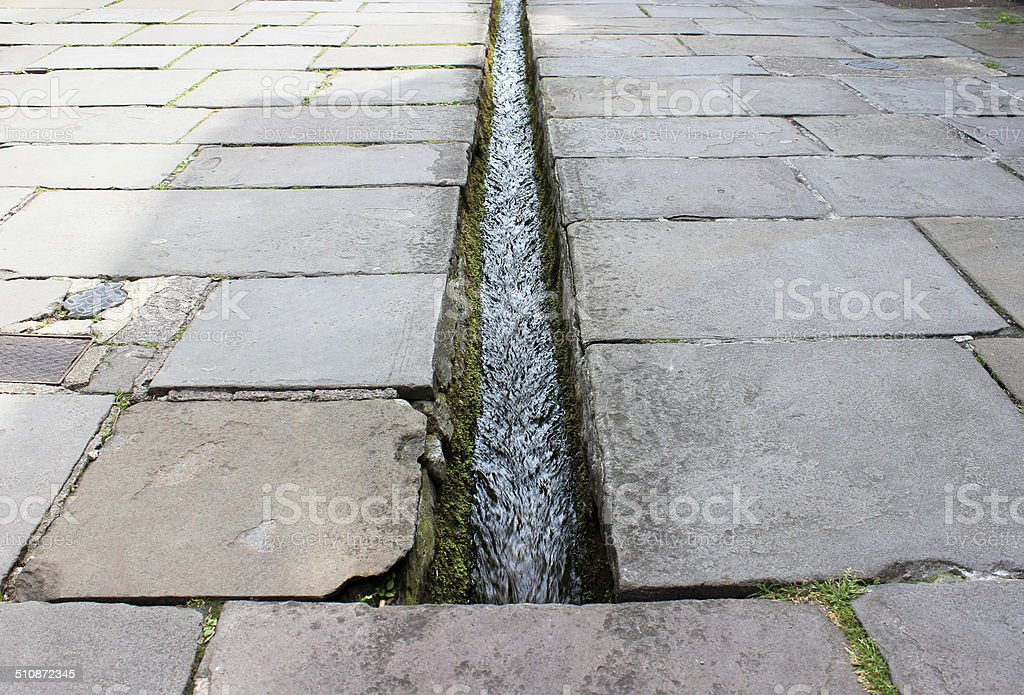 Small stream / rill running down centre of flagstone paved street stock photo