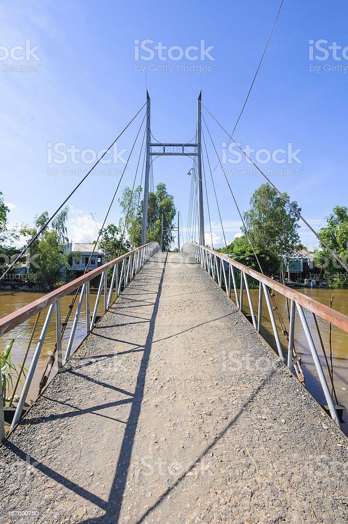 Small suspension bridge leading to a village stock photo