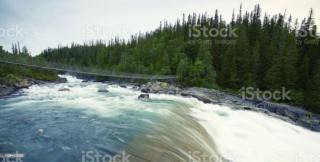 Small swedish suspenion bridge across waterfall stock photo
