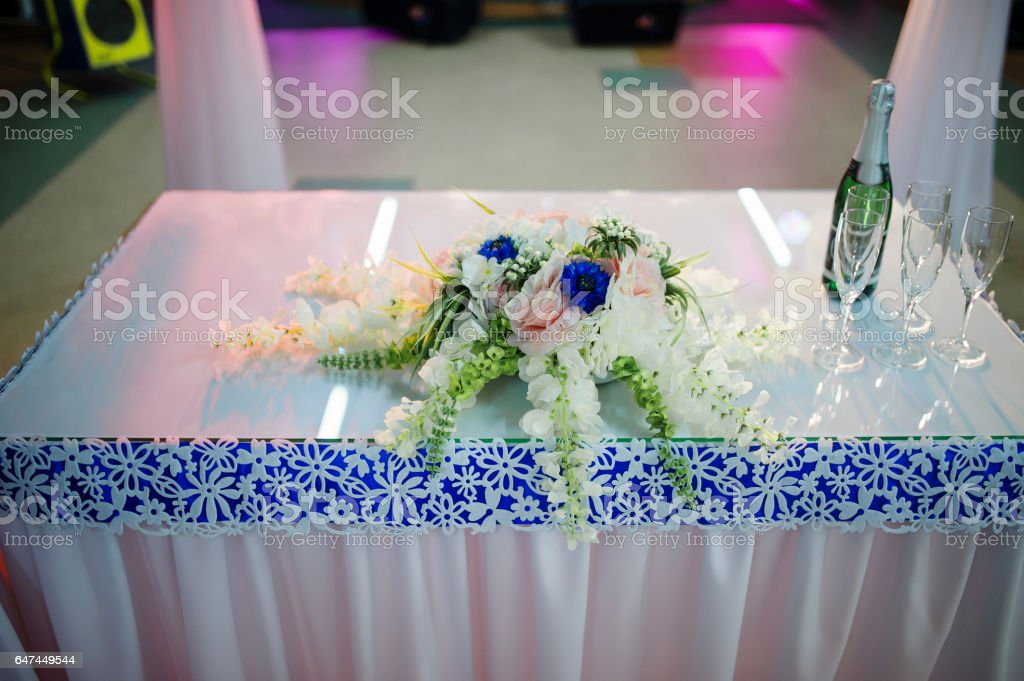 Small table wit bouquet and champagne with glasses on wedding reception. stock photo