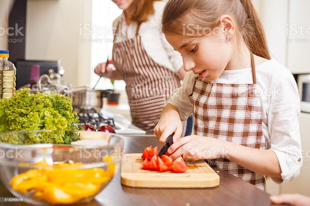 Small teenage girl cutting tomatoes in salad stock photo