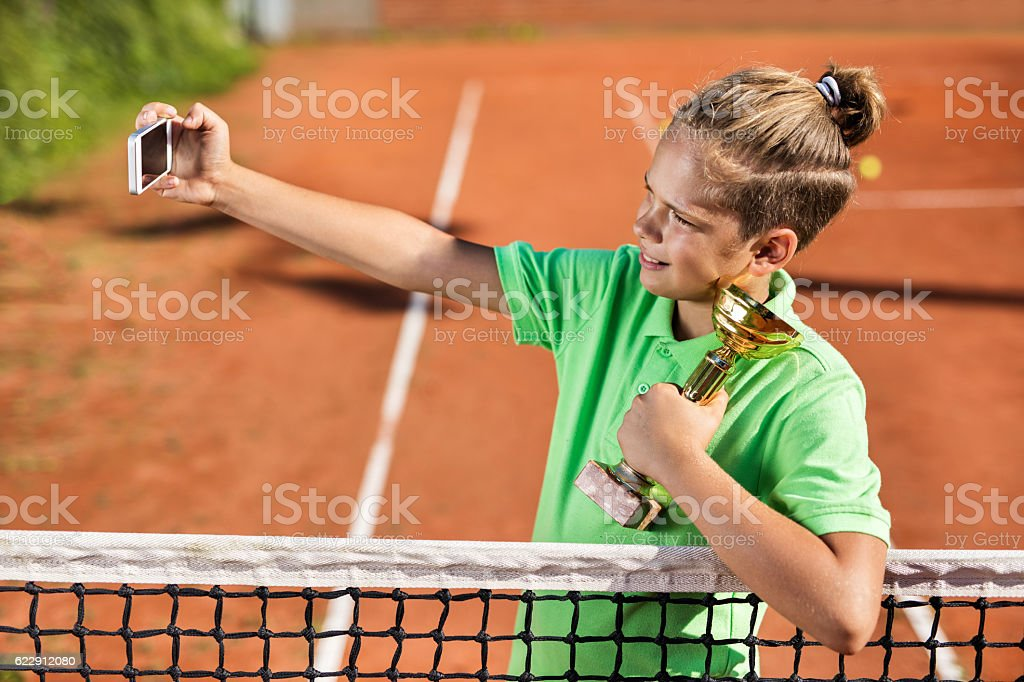 Small tennis player holding winning and trophy taking selfie. stock photo