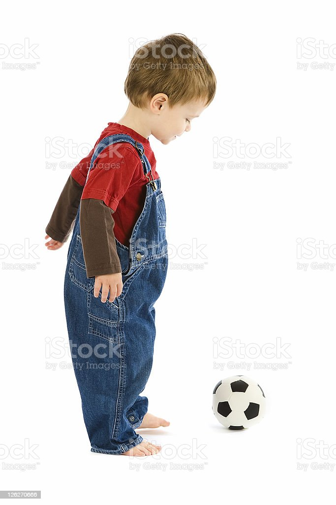 Small toddler playing football on white background stock photo