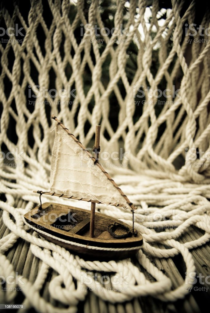 Small Toy Boat on Wooden Deck with Old Fishing Net royalty-free stock photo