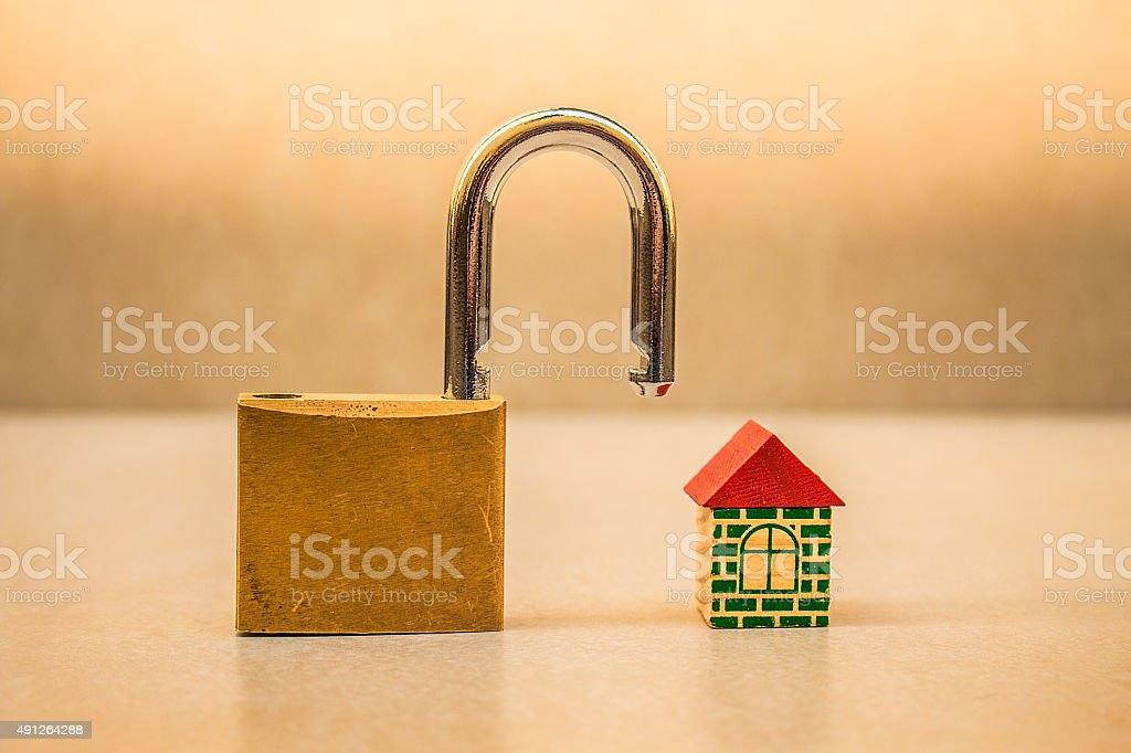 Small toy house and padlock stock photo