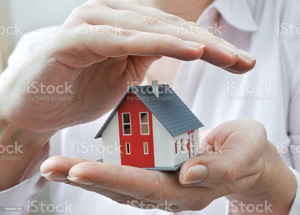A small toy house being held by a hand stock photo