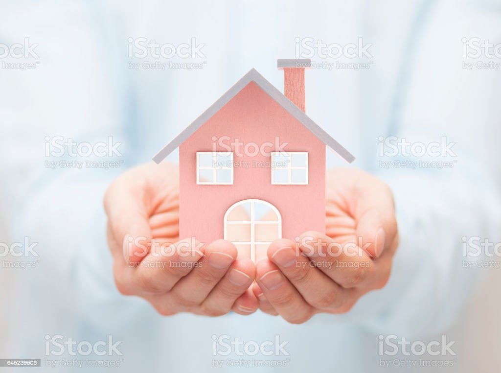 Small toy house in hands stock photo