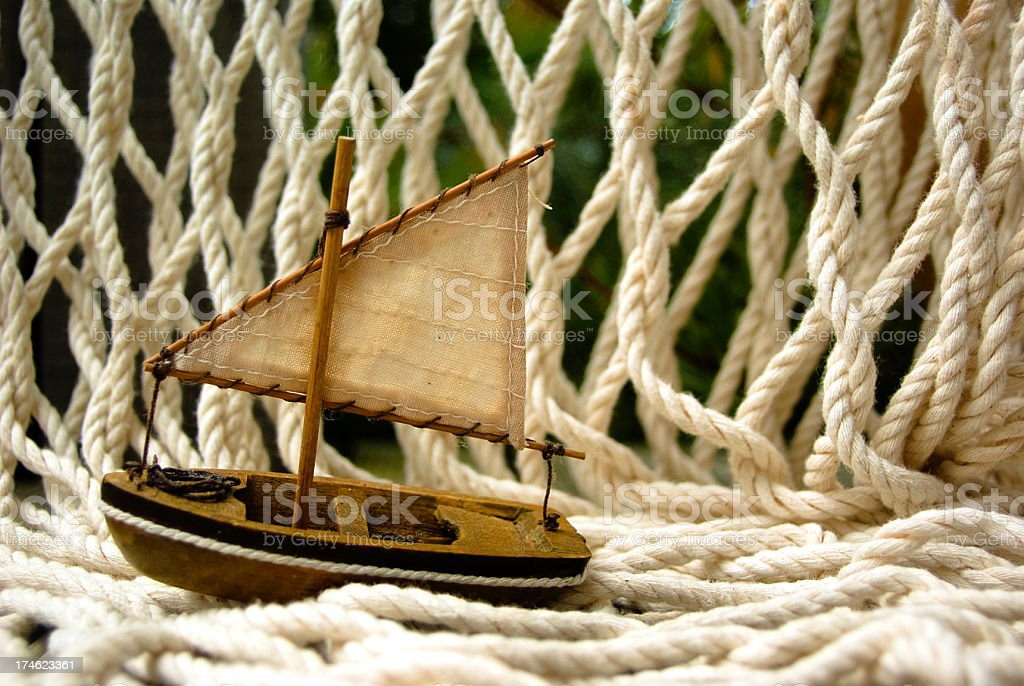 Small toy sail boat on wooden deck with fishing net stock photo
