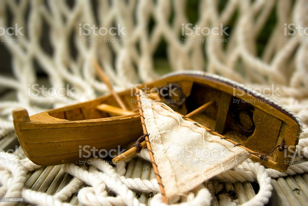 Small Toy sail boats on wooden deck with fishing net royalty-free stock photo