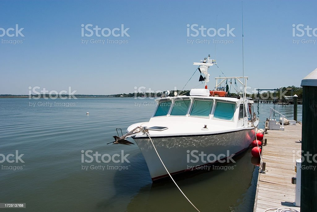 Small Trawling boat tied to a dock stock photo