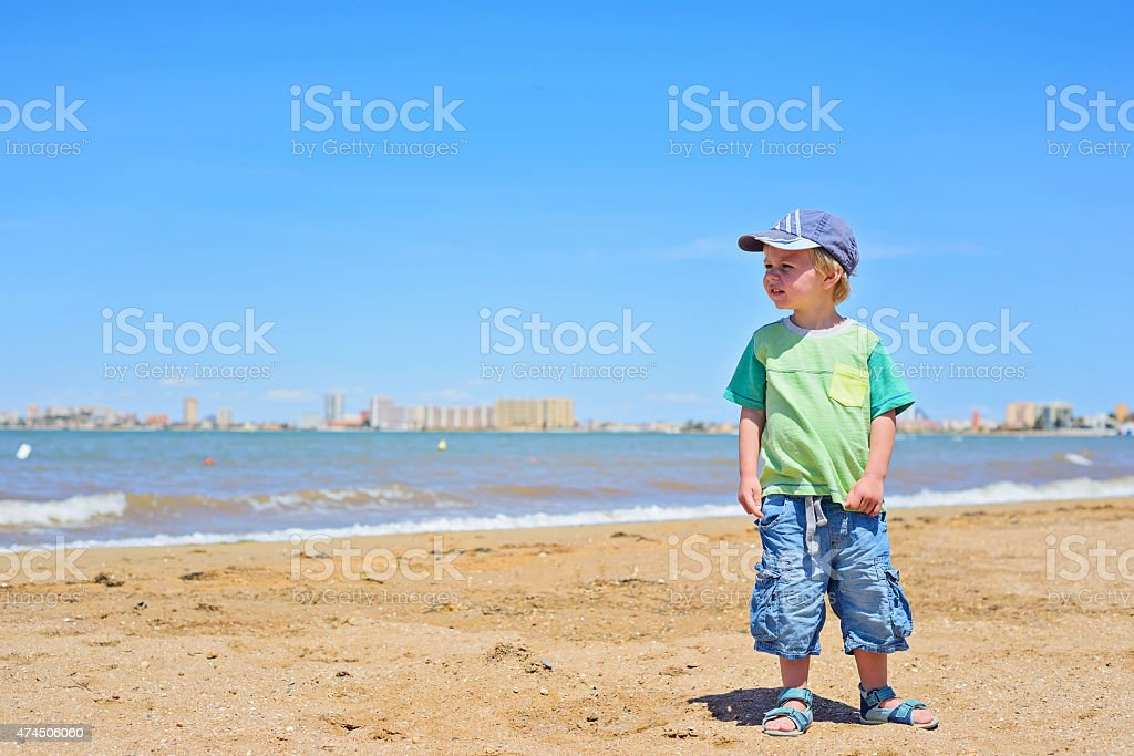 Small trendy boy standing sandy beach stock photo