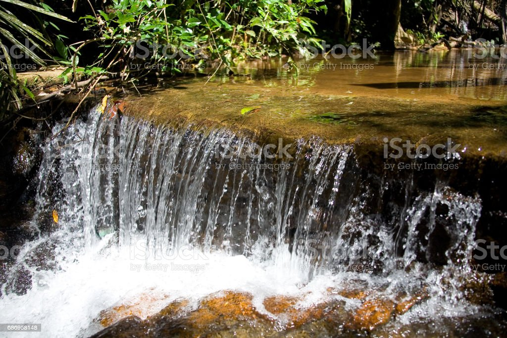 A small tropical waterfall with clear water. stock photo
