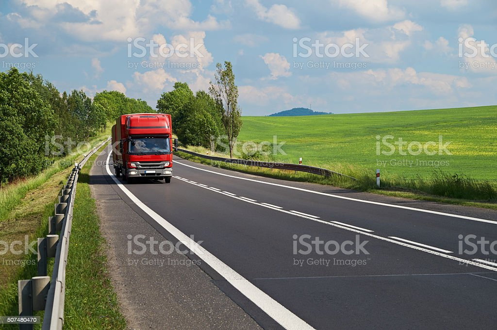 Small truck traveling on the asphalt road in a landscape stock photo