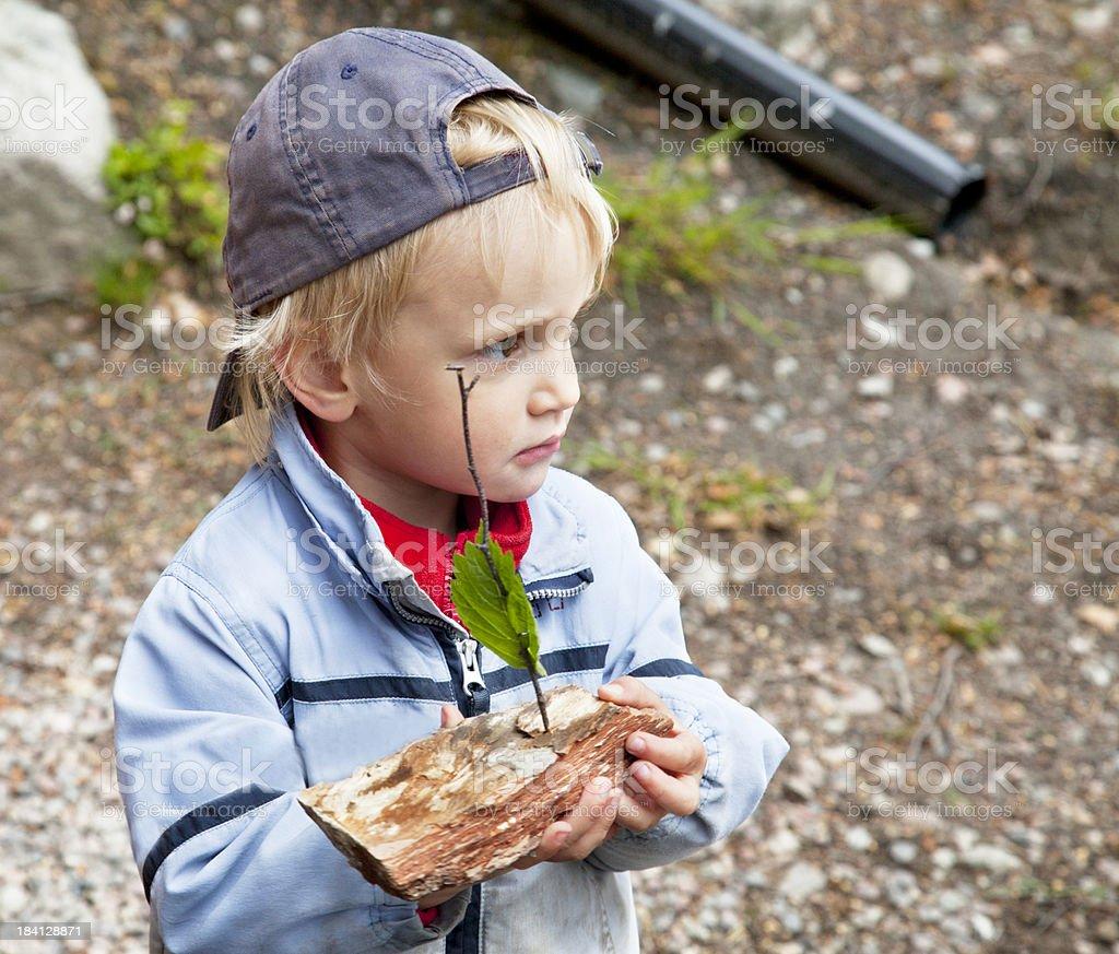 Small tuff boy with bark boat outdoors. royalty-free stock photo