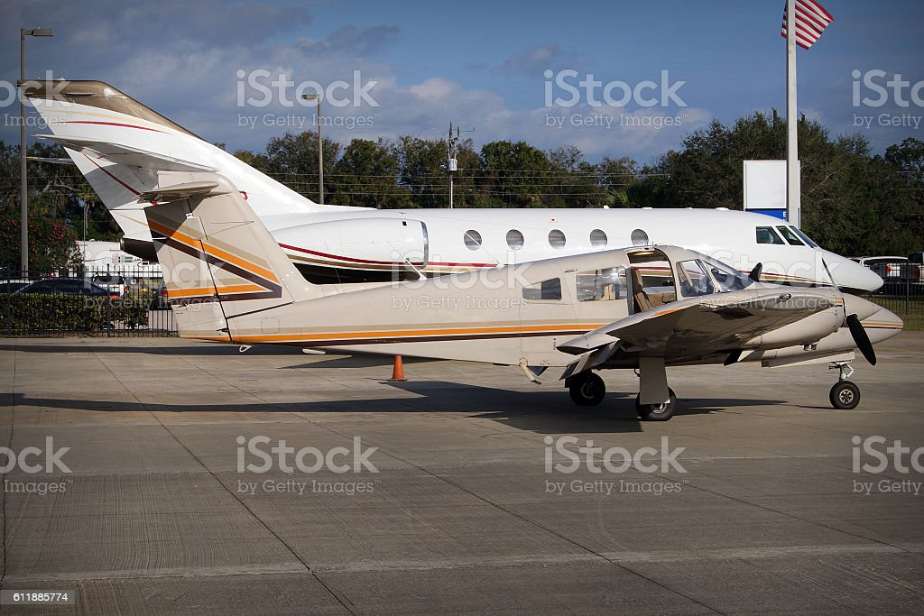 Small twin engine airplane and modern business jet stock photo
