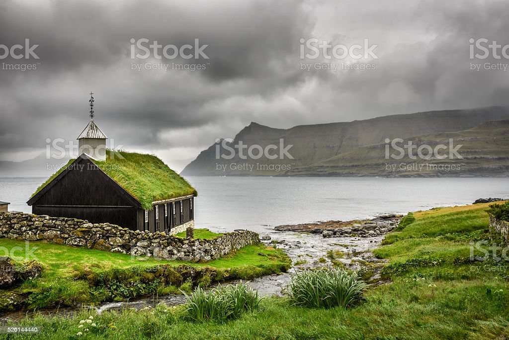 Small village church under heavy clouds stock photo