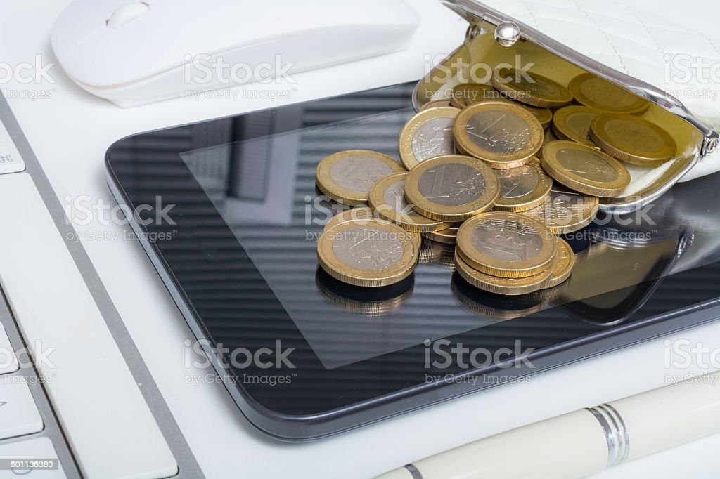 Small wallet filled with euro coins covers small digital tablet stock photo