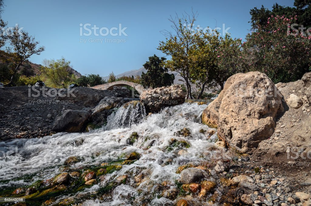 Small waterfall and old arch on a background stock photo