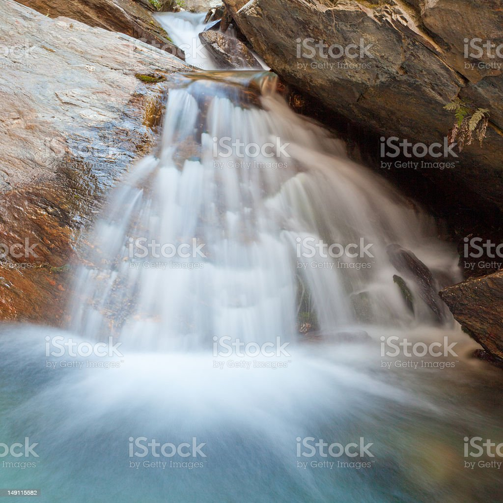 Small waterfall casdcading over rocks in blue pond royalty-free stock photo