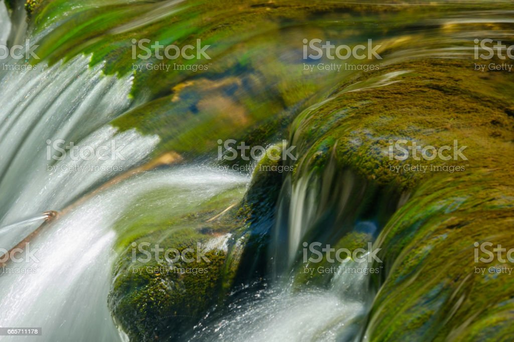 Small waterfall flowing over mossy rocks stock photo