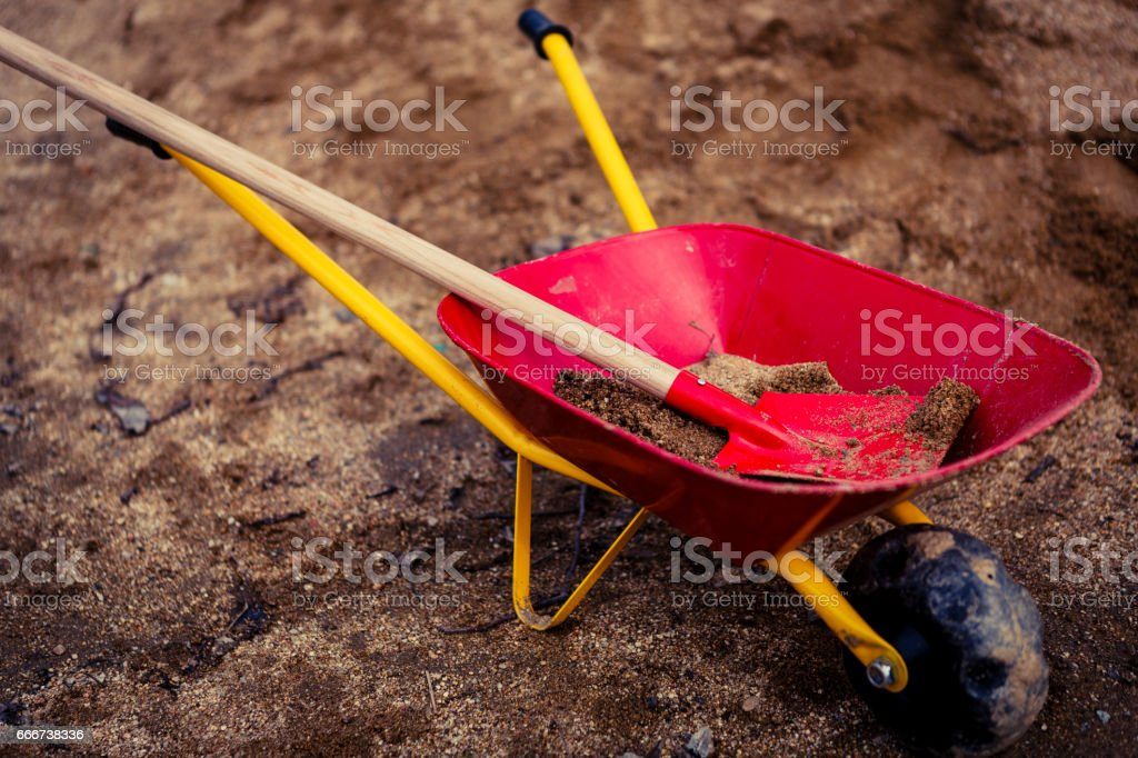 small wheelbarrow or barrow with sand - playground stock photo