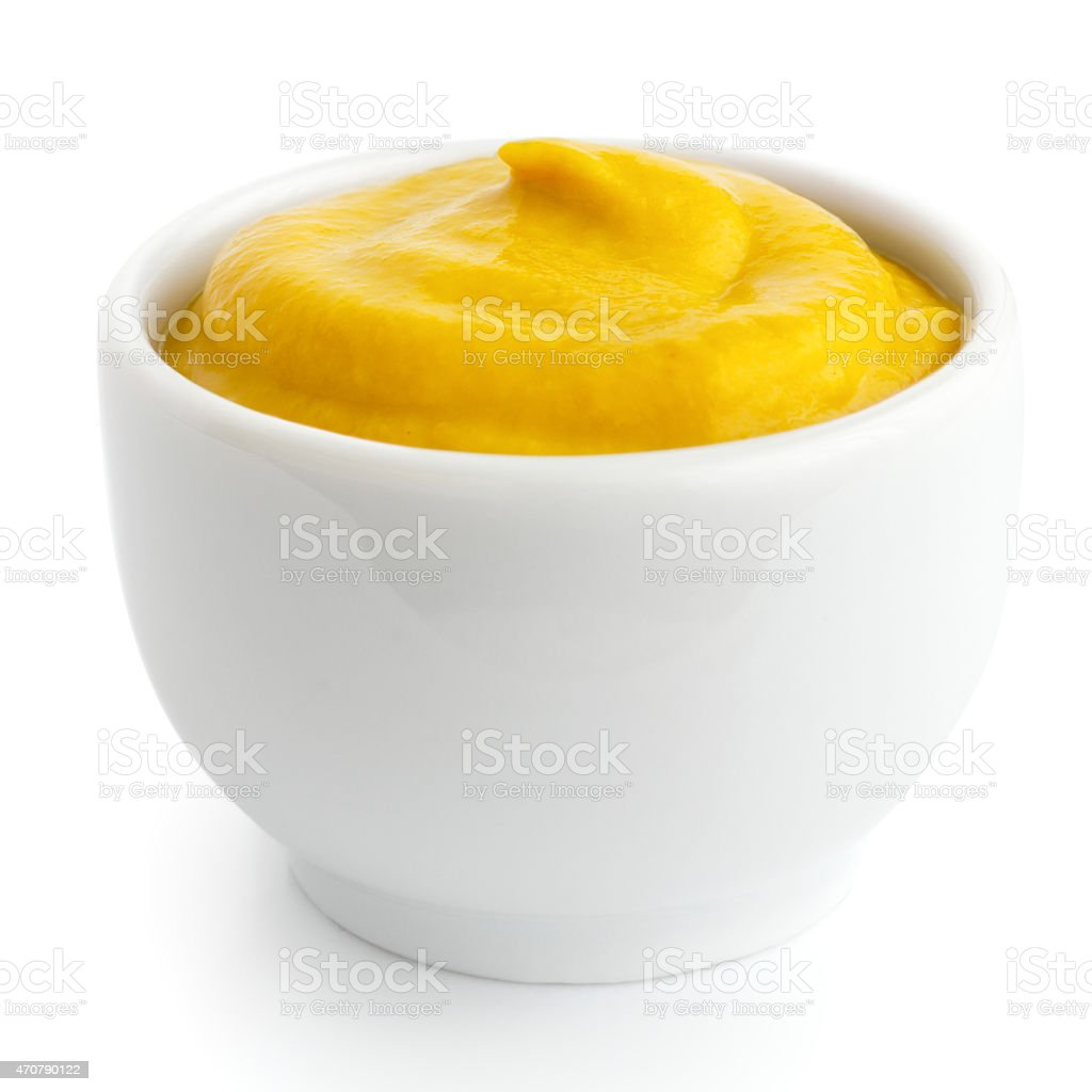 A small white ceramic dish with yellow american mustard stock photo