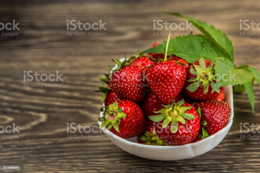 Small white china bowl filled with succulent juicy fresh ripe red strawberries on an old wooden textured table top. Fresh strawberries. strawberries on a wooden table stock photo