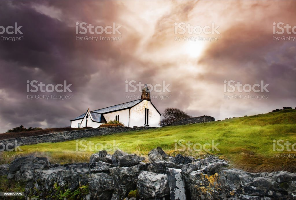 Small white church with cross and bell in dramatic cloudy sky stock photo
